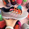 編まれる女子学生はスニーカーの履物の靴を遊ばす