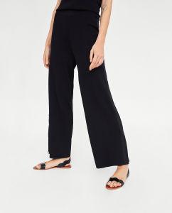 同じカラーの側面の縞の細部が付いている広足のニットのズボン
