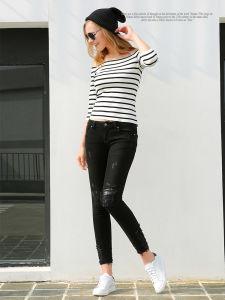 女性のばねの新式の裂かれ、伸縮性がある細く黒いジーンズ