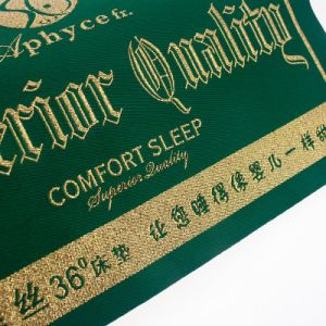 Costuras de alta calidad de tejido de hilo de oro sobre un colchón de la etiqueta principal