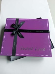 バレンタインデーのリボンが付いている紫色のハンドメイドチョコレートボックス