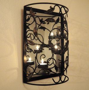 ミラーが付いている壁に取り付けられた金属の蝋燭ホールダー