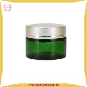 黒いプラスチックふたが付いている緑のクリーム色の装飾的なガラス瓶