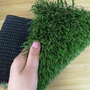 人工的なフットボールは泥炭のカーペットのサッカーを遊ばす