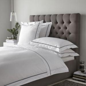 贅沢で白い綿の80年代のサテンの寝具はホテルのためにセットした